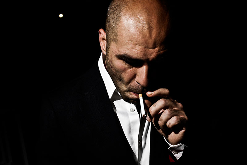 A tough man smoking a cigarette, high contrast image, single light source, hand held off camera flash, low-key photo