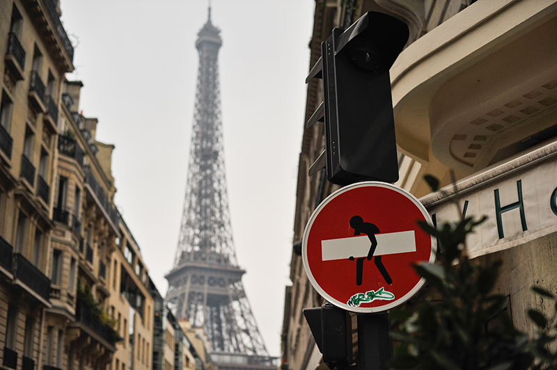 Unusual view of the Eiffel Tower, with man carrying a bar on a street sign. Local graffiti