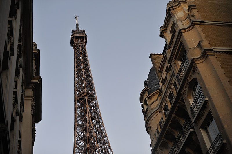 looking up at he Eiffel tower, through buildings