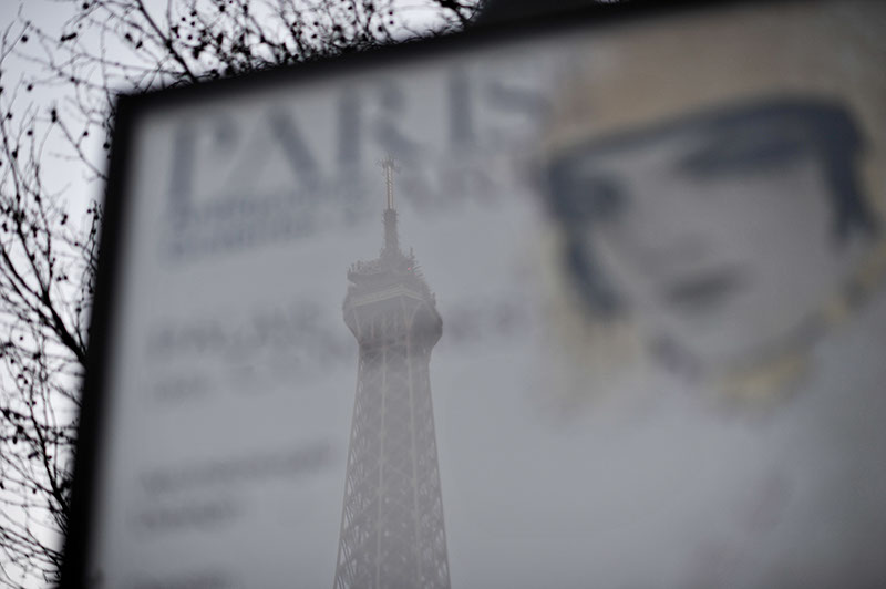 A reflection of the Eiffel tower in a display sign with the words Paris clearly visible