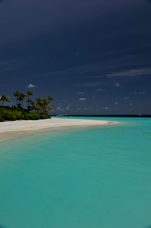 The turquoise waters white sands and blue sky of an uninhabited island in the Maldives