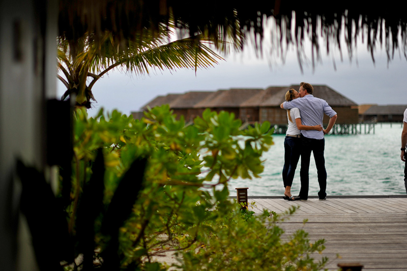 A honeymoon couple wait at the jetty for a private transfer to a nearby-uninhabited island; Champagne a 6-course meal and 10 staff members await their arrival